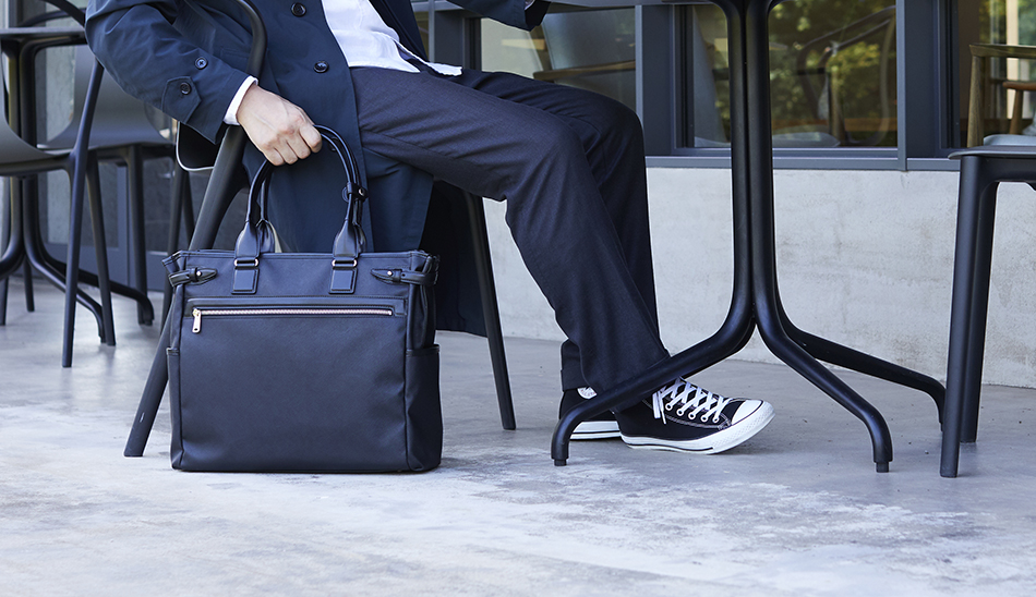 RAIZON ビジネスバッグを足元に置く男性 YURI CO.,LTD.